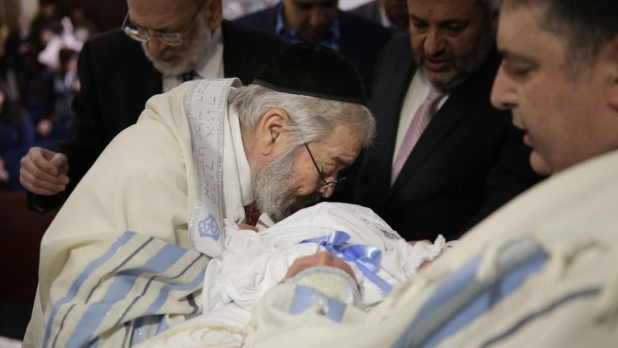 FILE- In this Feb. 11, 2015 file photo, Abraham Romi Cohn performs the oral suction during the bris, or ritual circumcision, of Yosef Sananas in New York. Reversing a policy that pitted health officials against religious leaders over a practice that dates to biblical times, the New York City Board of Health will no longer require parents to sign acknowledgements of potential health risks when their children undergo oral circumcision, Wednesday, Sept. 9, 2015. (AP Photo/Seth Wenig, File)