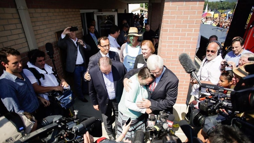 Rowan County clerk Kim Davis, center, hugs her attorney, Matt Staver, with Republican presidential candidate Mike Huckabee, centerr left, next to her after being released from the Carter County Detention Center, Tuesday, Sept. 8, 2015, in Grayson, Ky. Davis, the Kentucky county clerk who was jailed for refusing to issue marriage licenses to gay couples, was released Tuesday after five days behind bars. (Jonathan Palmer/The Courier-Journal via AP) NO SALES; MAGS OUT; NO ARCHIVE; MANDATORY CREDIT