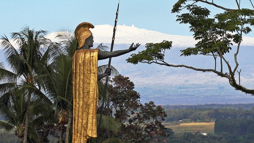 FILE - This Jan. 31, 2014, file photo, shows a statue of Hawaiian King Kamehameha I with snow-capped Mauna Kea in the distance, in Hilo, Hawaii. (AP Photo/Tim Wright, File)