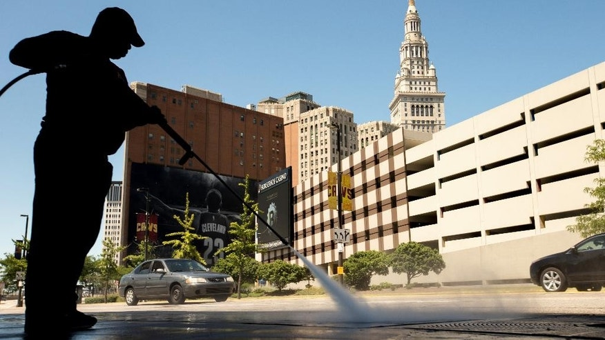 FILE - In this Aug. 5, 2015 file photo, a worker cleans the sidewalk in front of the Quicken Loans Arena in Cleveland. The Labor Department releases its job openings and labor turnover survey for July on Wednesday, Sept. 9, 2015. (AP Photo/Andrew Harnik, File)