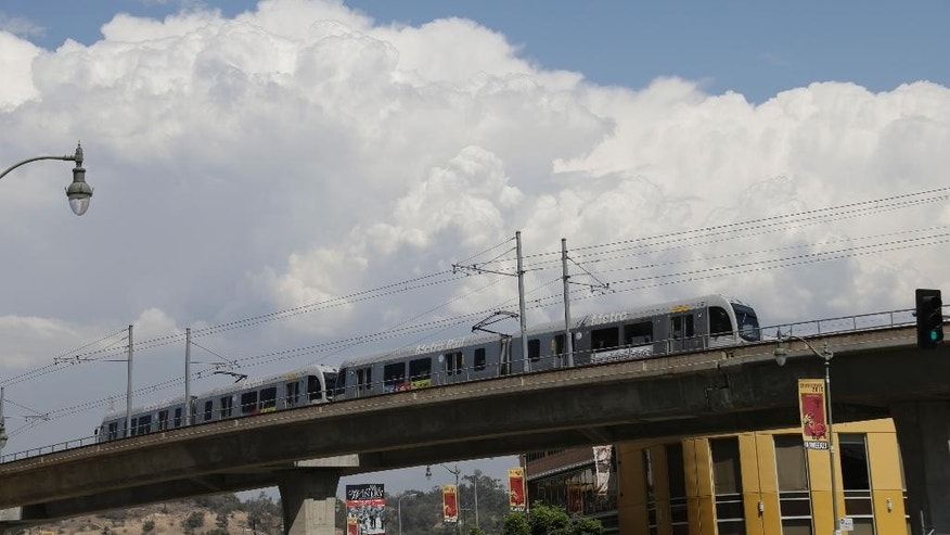 Thunderhead cloud formations are seen over the Metro Rail on the Metro Gold line downtown Los Angeles Wednesday, Sept.  9, 2015. Southern California will see dangerously high temperatures this week and a chance of thunderstorms and flooding in the mountains as a building high-pressure system delivers a late-summer scorching, forecasters said Tuesday. (AP Photo/Nick Ut)