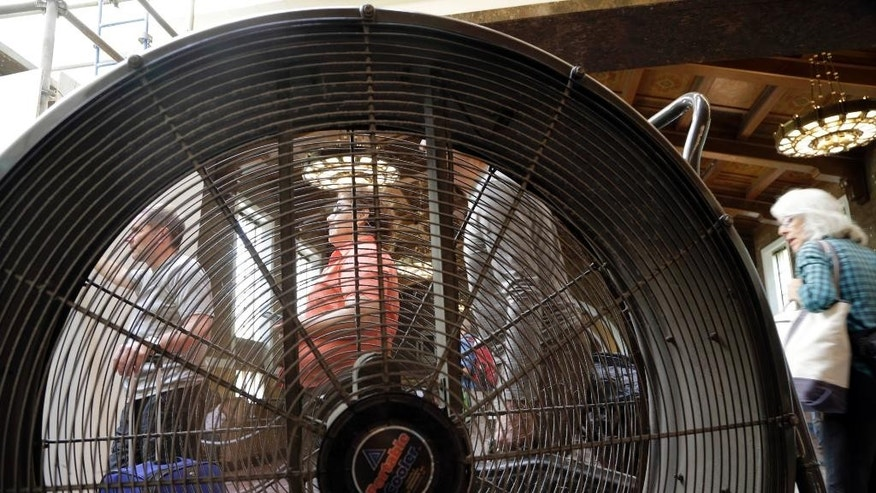 Travelers stand in line behind a big electric fan at Los Angeles Union Station in Los Angeles, Wednesday, Sept. 9, 2015. Temperatures reached 99 degrees before noon in downtown Los Angeles. Hundreds of cooling centers are open in senior centers and libraries around the state as excessive heat warnings were issued into tomorrow night in many areas, especially the valleys and lower mountain elevations. (AP Photo/Nick Ut)