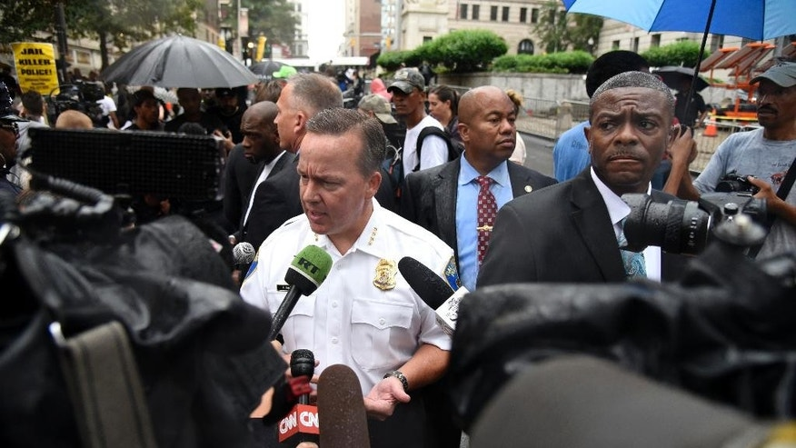 Interim Baltimore City Police Commissioner Kevin Davis speaks to members of the news media as protesters demonstrate outside the Baltimore Circuit Court on Thursday, Sept. 10, 2015 in Baltimore.  The trials for six police officers charged in the arrest and death of Freddie Gray will be held in Baltimore, Circuit Court Judge Barry Williams ruled, saying it would be nearly impossible to find a place not inundated by publicity about the high-profile.  (Barbara Haddock Taylor/The Baltimore Sun via AP)  WASHINGTON EXAMINER OUT; MANDATORY CREDIT