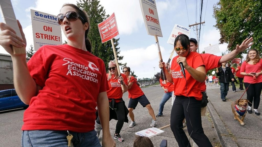 Teachers Sarah Martin, left, and Ina Shepard, with microphone, lead cheers during picketing in front of Chief Sealth International High School Wednesday, Sept. 9, 2015, in Seattle. Teachers in Seattle began walking picket lines Wednesday after last-minute negotiations over wages and other issues failed to avert a strike in Washington state's largest school district. Classes for 53,000 Seattle Public Schools students were canceled Wednesday, on the scheduled first day of school. (AP Photo/Elaine Thompson)