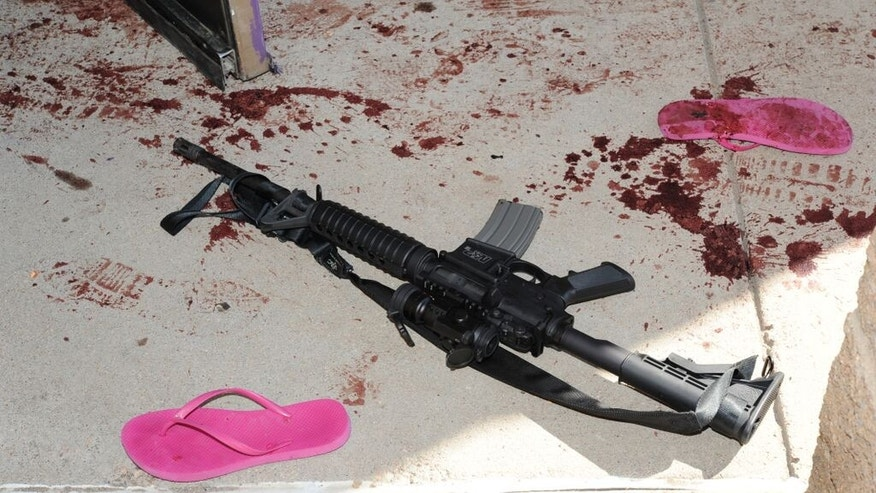 This July 2012 evidence photo, which the Arapahoe County District Attorney's Office released in response to open-records requests, shows an assault weapon and blood by sandals following the July 20, Colorado theater shooting by James Holmes in Aurora, Colo. In August 2015, Holmes was sentenced to life in prison because jurors could not agree that he deserved the death penalty. (Arapahoe County District Attorney's Office via AP)