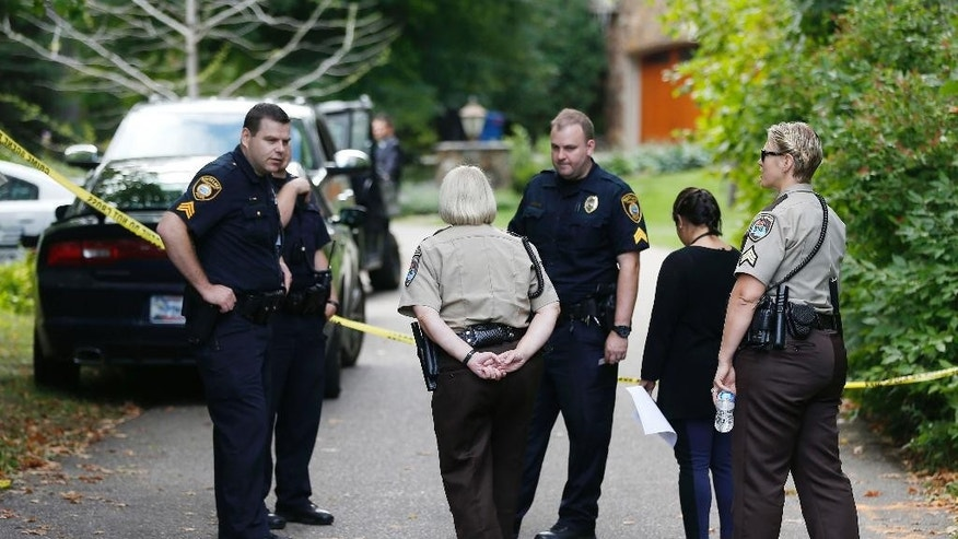 Police and deputies gather at the entrance to the road leading to a lakeside home where police said five family members, including three children, were found dead Thursday, Sept. 10, 2015 in Greenwood, Minn., an upscale western Minneapolis suburb in what police said appeared to be a murder-suicide. (AP Photo/Jim Mone)