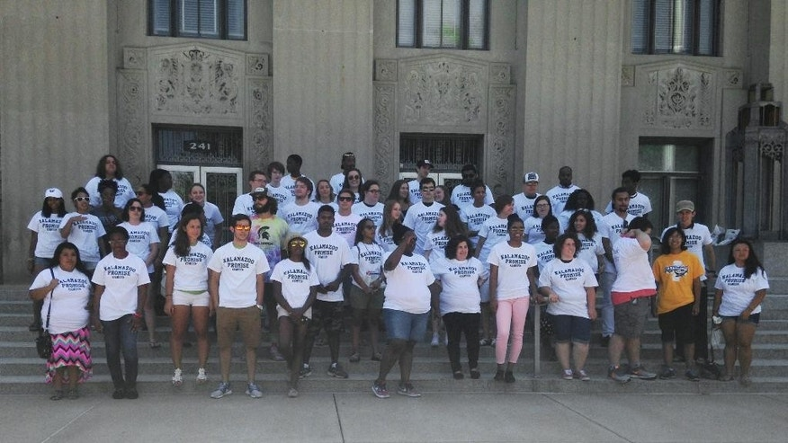 Kalamazoo Promise recipients pose for a group photo during an event celebrating the 10-year anniversary of the anonymously funded program on Saturday, Aug. 15, 2015, in Kalamazoo, Mich. Announced in 2005, the Kalamazoo Promise, which pays the college tuition of students from the Kalamazoo public school district, has given out $67 million in scholarships, and students have earned more than 850 degrees and post-secondary credentials. Close to 4,000 students have taken advantage. (AP Photo/ Mike Householder)