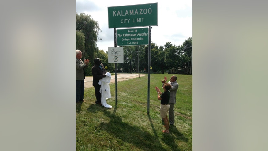 Kalamazoo Promise Executive Director Bob Jorth, from left, Kalamazoo Mayor Bobby Hopewell, former Kalamazoo Promise Executive Director Janice Brown and Kalamazoo Promise Executive Director of Community Relations Von Washington Jr. applaud Friday, Aug. 14, 2015, in Kalamazoo, Mich., following the unveiling of city limit signs honoring the Kalamazoo Promise and its 10-year anniversary. Announced in 2005, the anonymously funded program that pays the college tuition of students from the Kalamazoo public school district has given out $67 million in scholarships, and students have earned more than 850 degrees and post-secondary credentials. Close to 4,000 students have taken advantage. (AP Photo/ Mike Householder)