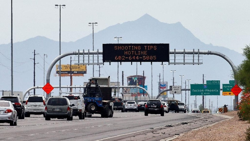 An Arizona Department of Transportation sign gives a hotline number for information on the recent freeway shootings as motorists pass under at the 202/I-10 intersection, Wednesday, Sept. 9, 2015 in Chandler, Ariz. Authorities are investigating nine shootings of vehicles over the past two weeks along I-10 in Phoenix. A truck's passenger window shattered on a Phoenix freeway Wednesday as Arizona authorities investigated a string of highway shootings that have rattled nerves and heightened fears of a possible serial shooter.(AP Photo/Matt York)