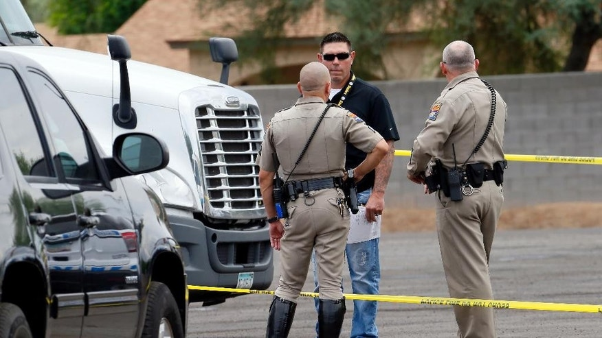 Arizona Department of Public Safety officers stand near a tractor trailer shortly after it was shot near 67th Ave and I-10, Thursday, Sept. 10, 2015 in Phoenix. Numerous shootings of vehicles along I-10 over the past two weeks have investigators working around the clock to find a suspect in a spate of recent Phoenix freeway shootings that have rattled nerves and heightened fears of a possible serial shooter. (AP Photo/Matt York)