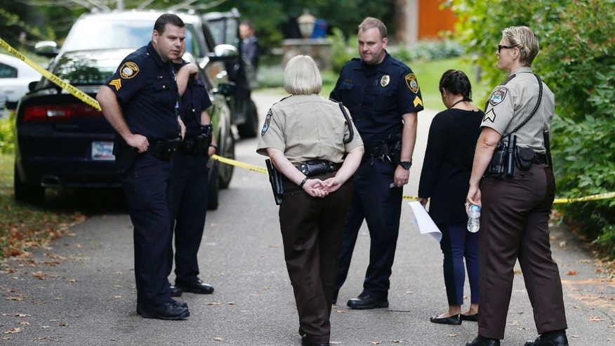 Sept. 10, 2015: Police and deputies gather at the entrance to the road leading to a lakeside home where police said five family members, including three children, were found dead in Greenwood, Minn.