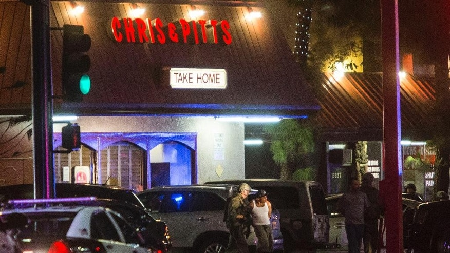 Los Angeles County sheriff's SWAT team escort two andcuffed men out of Chris' and Pitt's barbecue restaurant after an armed carjacking suspect who led officers and deputies on a high-speed chase was holed up in the restaurant, Thursday, Sept. 10, 2015 in Downey, Calif.   (AP Photo/Ringo H.W. Chiu)