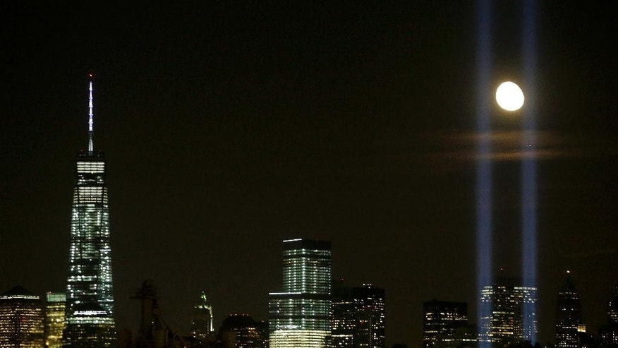 FILE- In this Sept. 11, 2014 file photo, the moon appears between the beams from the Tribute in Light memorial honoring the victims of the Sept. 11 terrorist attacks as 1 World Trade Center, left, stands on the 13th anniversary as seen from Jersey City, N.J. The Tribute in Light, which first appeared on March 11, 2002, to mark the six months that had passed since the attacks. It has become a moving, quietly powerful element of the anniversaries since. (AP Photo/Julio Cortez, File)