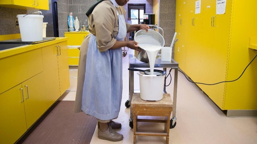 Poor Clares nun Sister Thereza pours a mixture of water and flour to make altar bread also known as communion wafers, Tuesday, Sept. 8, 2015, at the Monastery of Saint Clare in Langhorne, Pa. The nuns are helping to supply wafers for the scheduled Mass being celebrated by Pope Francis on Sept. 27. (AP Photo/Matt Rourke)
