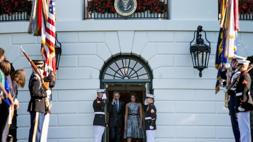 President Barack Obama and first lady Michelle Obama arrive on the South Lawn of the White House in Washington, Friday, Sept. 11, 2015, to observe a moment of silence to mark the 14th anniversary of the 9/11 attacks. (AP Photo/Andrew Harnik)