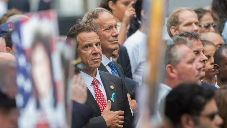 New York Gov. Andrew Cuomo and former Gov. George Pataki attend a ceremony at the World Trade Center site in New York on Friday, Sept. 11, 2015. Sept. 11 victims' relatives marked the anniversary of the terror attacks Friday in a subdued gathering at ground zero, saying their determination to commemorate their loss publicly hadn't dimmed even as 14 years have passed and crowds at the ceremony have thinned. (AP Photo/Bryan R. Smith)