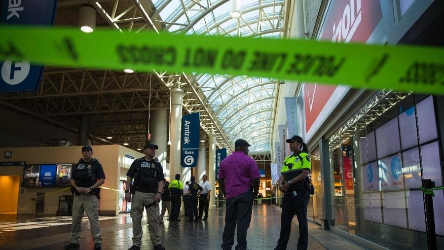 Police and emergency responders stand outside a McDonald's located inside Union Station in Washington, Friday, Sept. 11, 2015, after a security guard shot a suspect who attacked a worker with a knife at the restaurant. (AP Photo/Evan Vucci)