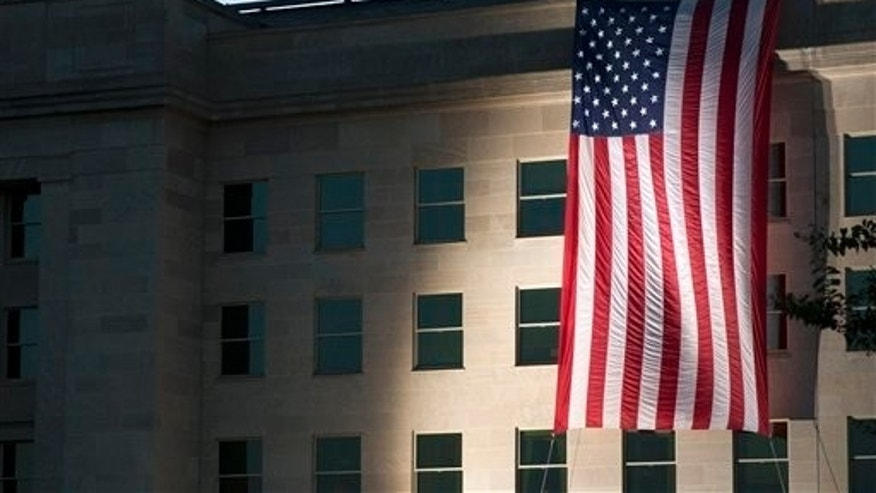 A U.S. flag is draped on the side of the Pentagon where the building was attacked on September 11th in 2001, on the 14th anniversary of the attack, Friday Sept. 11, 2015, in Washington. (AP Photo/Jacquelyn Martin)