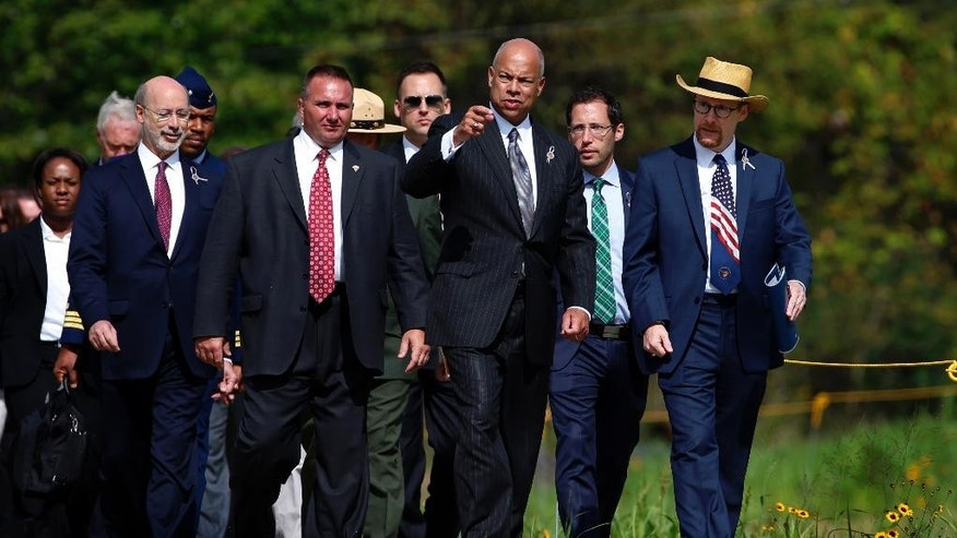 United States Secretary of Homeland Security Jeh Johnson, front center, and Gordon Felt, right, whose brother Edward was one of the 40 crew and passengers on United Flight 93, lead a group, including Pennsylvania Governor Tom Wolf, second from left,  down a path from the Flight 93 National Memorial  Visitors Center after a remembrance service in Shanksville, Pa, Friday, Sept. 11, 2015. (AP Photo/Gene J. Puskar)