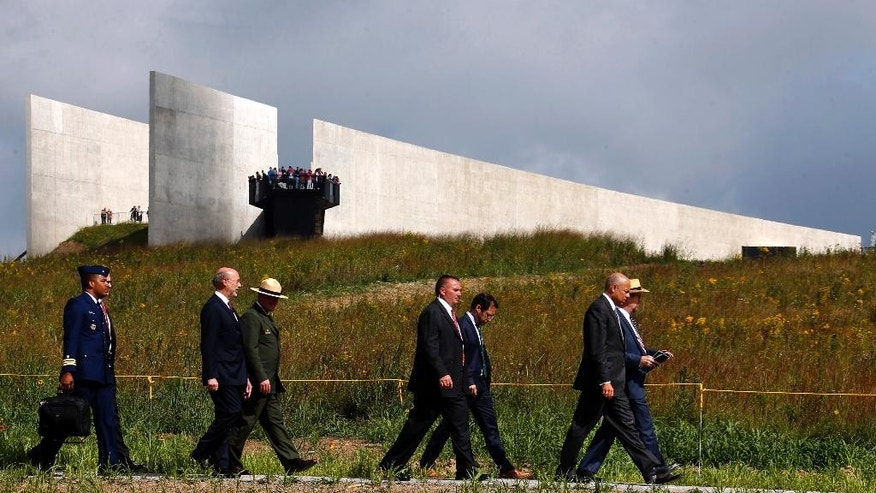 United States Secretary of Homeland Security Jeh Johnson,  front right, leads a group including Pennsylvania Governor Tom Wolf, second from left, down a path from the Flight 93 National Memorial  Visitors Center, rear, after a remembrance service in Shanksville, Pa, Friday, Sept. 11, 2015. Hundreds of victims' relatives gathered for what has become a tradition of tolling bells, moments of silence and the reading of the names of the nearly 3,000 people killed in the terror strikes at the World Trade Center, the Pentagon and a field near Shanksville, Pennsylvania.(AP Photo/Gene J. Puskar)