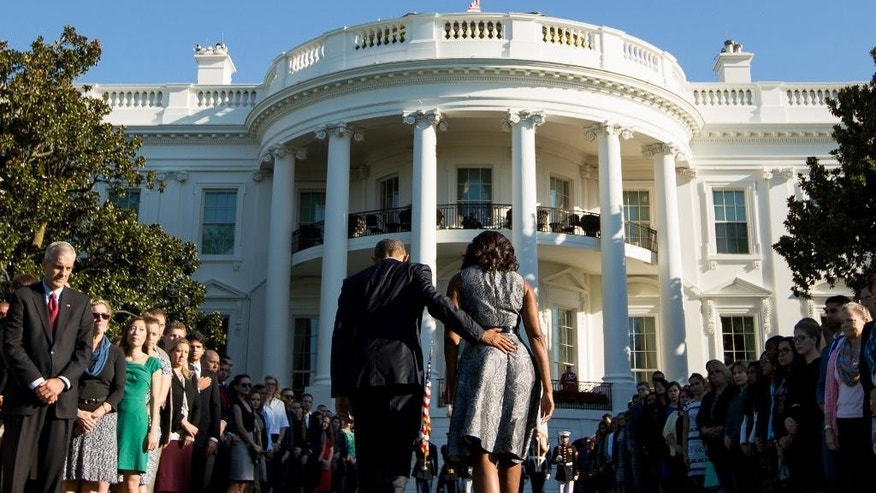 President Barack Obama and first lady Michelle Obama leave the South Lawn of the White House in Washington, Friday, Sept. 11, 2015, after observing a moment of silence to mark the 14th anniversary of the 9/11 attacks. (AP Photo/Andrew Harnik)