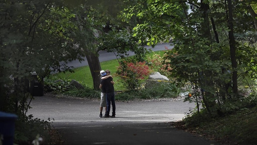 Nick Collins, right, embraces Minnetonka High School classmate Nathan Kahn during a visit Friday, Sept. 11, 2015, to the scene where five family members were found inside a home in Greenwood, Minn. Police pushed ahead Friday with their investigation into an apparent murder-suicide in the affluent Minneapolis suburb that left a family of five dead, while a high school offered counseling to classmates of the three children. (Jim Gehrz/Star Tribune via AP)  MANDATORY CREDIT; ST. PAUL PIONEER PRESS OUT; MAGAZINES OUT; TWIN CITIES LOCAL TELEVISION OUT