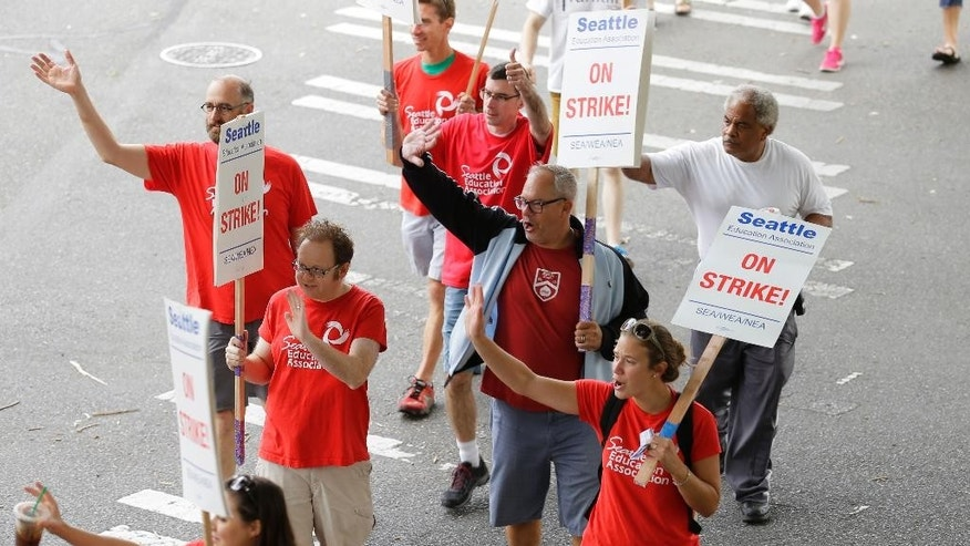 Striking Seattle School District teachers and other educators  wave to motorists as they walk a picket line, Thursday, Sept. 10, 2015, in front of Franklin High School in Seattle. The strike was called when Seattle Public Schools and the teachers union failed to reach an agreement on their contract Tuesday night, and is Seattle's first educator strike in 30 years. (AP Photo/Ted S. Warren)
