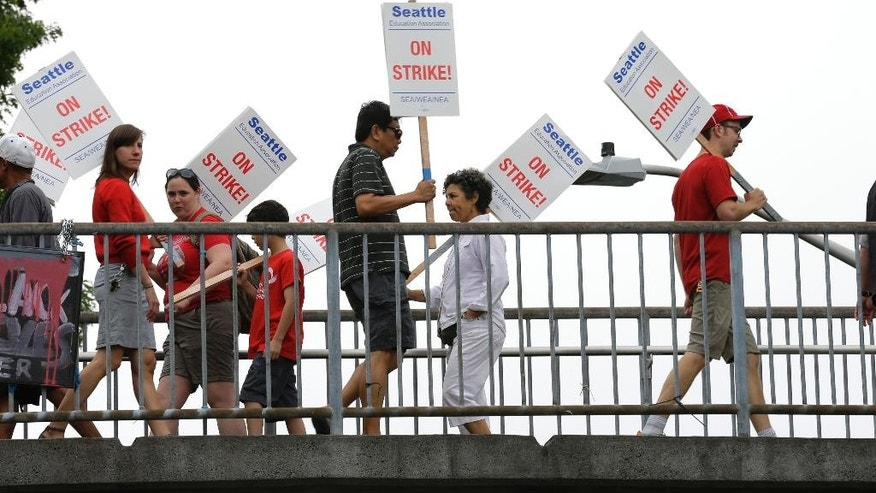 Striking Seattle School District teachers and other educators walk a picket line on a pedestrian overpass, Thursday, Sept. 10, 2015, in front of Franklin High School in Seattle.  The strike comes as teachers in Seattle have gone six years without a cost-of-living pay increase. (AP Photo/Ted S. Warren)