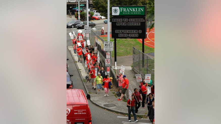 Striking Seattle School District teachers and other educators walk a picket line, Thursday, Sept. 10, 2015, in front of Franklin High School in Seattle. The strike was called when Seattle Public Schools and the teachers union failed to reach an agreement on their contract Tuesday night, and is Seattle's first educator strike in 30 years. (AP Photo/Ted S. Warren)
