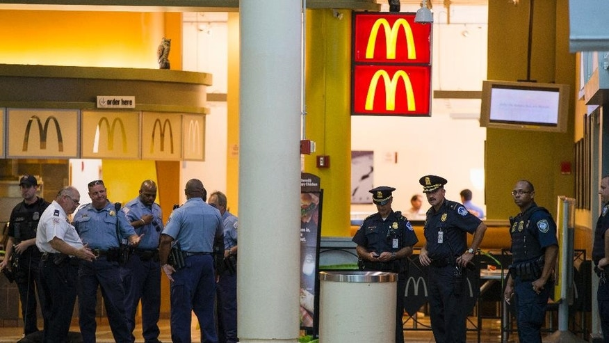 Police and emergency responders stand outside a McDonald's located inside Union Station in Washington, Friday, Sept. 11, 2015, after a security guard shot a man who stabbed a woman inside Union Station on Friday, the anniversary of the September 11 attacks, District of Columbia police said. (AP Photo/Evan Vucci)