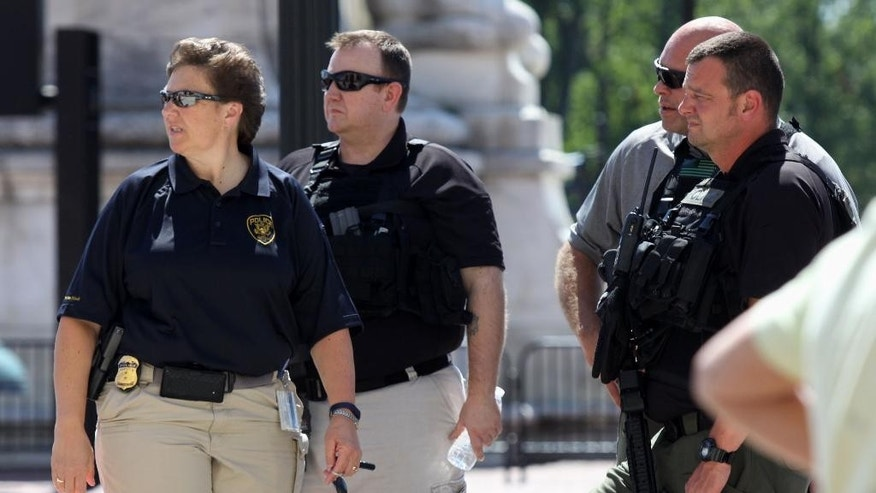 Police officers stand outside Union Station in Washington, Friday, Sept. 11, 2015, after a security guard shot a man who stabbed a woman inside, the anniversary of the September 11 attacks, District of Columbia police said.  (AP Photo/Lauren Victoria Burke)