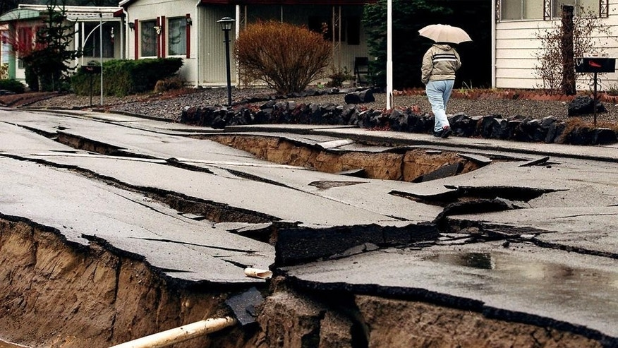 File-In this March 1, 2001, file photo, Ann Rice walks passed earthquake damage in Tumwater, Wash.  When North America's undersea edge and a tectonic plate pushing beneath it inevitably give way to three centuries of accumulated stress, unleashing a monster earthquake and tsunami in the Pacific Northwest, the expected catastrophic loss of life and economic disruptions could be lessened by an early warning system. (Dean J. Koepfler/The News Tribune via AP, file)  MANDATORY CREDIT