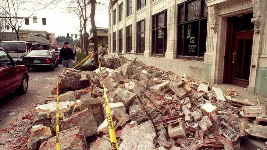 File--In this Feb. 28, 2001, file photo, a passerby looks at the damage to the ornate facade that broke off from the Washington Federal Savings building at Capitol Way and 5th Avenue in Olympia, Wash., after a powerful earthquake hit the Northwest region.  When North America's undersea edge and a tectonic plate pushing beneath it inevitably give way to three centuries of accumulated stress, unleashing a monster earthquake and tsunami in the Pacific Northwest, the expected catastrophic loss of life and economic disruptions could be lessened by an early warning system. (Bruce Kellman/The News Tribune via AP, file)  MANDATORY CREDIT