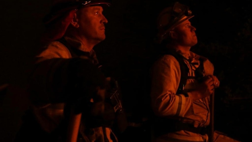 Firefighters Chris Wilkes, left, and Robert McKenzie, are seen in the orange glow of the flames of the Butte Fire burning near San Andreas, Calif., Friday, Sept. 11, 2015. (AP Photo/Rich Pedroncelli)