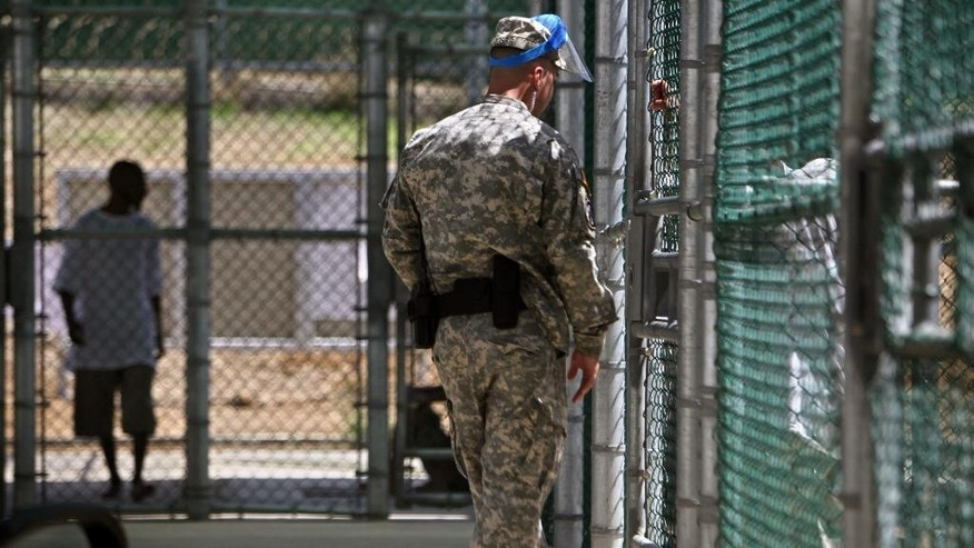 FILE - In this May 31, 2009 pool-file photo reviewed by the U.S. military and shot through a window, a guard wearing a protective face mask speaks with a detainee through a fence as another paces inside the exercise yard at Camp five detention facility on Guantanamo Bay U.S. Naval Base in Cuba. The Obama Administration's struggling crusade to close the U.S. detention center at Guantanamo Bay, Cuba, is mired in state and federal politics, and frustrated White House and Pentagon officials are blaming each other for the slow progress releasing approved detainees and finding a new prison to house the remainder. (AP Photo/Brennan Linsley, Pool, File)