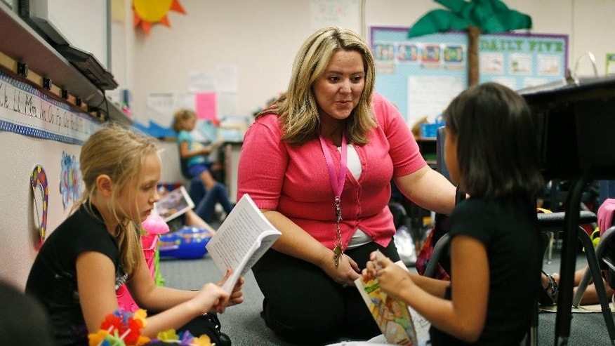Sept. 10, 2015: Tia Martin, center, works with Izabel Martinez, left, and Ashlyn Dowding in a third-grade class at Ulis Elementary School in Henderson, Nev.