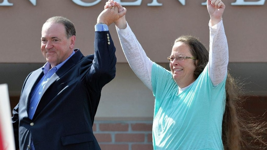 FILE - In this Tuesday, Sept. 8, 2015, file photo, Rowan County Clerk Kim Davis, with Republican presidential candidate Mike Huckabee at her side, greets the crowd after being released from the Carter County Detention Center, in Grayson, Ky. Having failed to ban same-sex marriage, many religious conservatives are now working to carve out protections for business owners and others who object to it on religious grounds. To some of them, Davis is a hero for her willingness to go to jail rather than issue marriage licenses. But others think Davis' position as a government official makes her exactly the wrong figure to rally around.  (AP Photo/Timothy D. Easley, File)