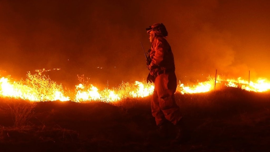 An inmate from the California Department of Corrections and Rehabilitation stands guard as flames from the Butte Fire approach a containment line Saturday, Sept. 12, 2015 near San Andreas, Calif.(AP Photo/Rich Pedroncelli)