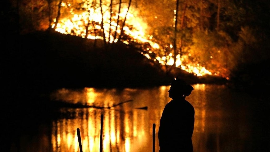 A firefighter stands near a wildfire in Middletown, Calif., on Sunday, Sept. 13, 2015. Two of California's fastest-burning wildfires in decades overtook several Northern California towns, killing at least one person and destroying hundreds of homes and businesses. (AP Photo/Elaine Thompson)