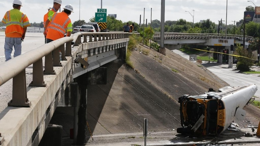 Highway workers look over the broken guard rail where a Houston school bus, right, drove off and flipped Tuesday, Sept. 15, 2015, in Houston.  A female student died at the scene of the wreck and a second girl died at a hospital, according to a statement by the Houston Independent School District.  Three others seriously injured  (AP Photo/Pat Sullivan)