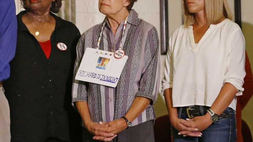 From left, Janie Coverdale, who lost two grandchildren in the Oklahoma City bombing, Nancy Norvell and Kathy Wokaty, a sister of death row inmate Richard Glossip, listen during a news conference in Oklahoma City, Monday, Sept. 14, 2015. Glossip is scheduled to be executed on Wednesday, Sept. 16, 2015, and his defense team is asking for a stay while they search for evidence in the case. (AP Photo/Sue Ogrocki)