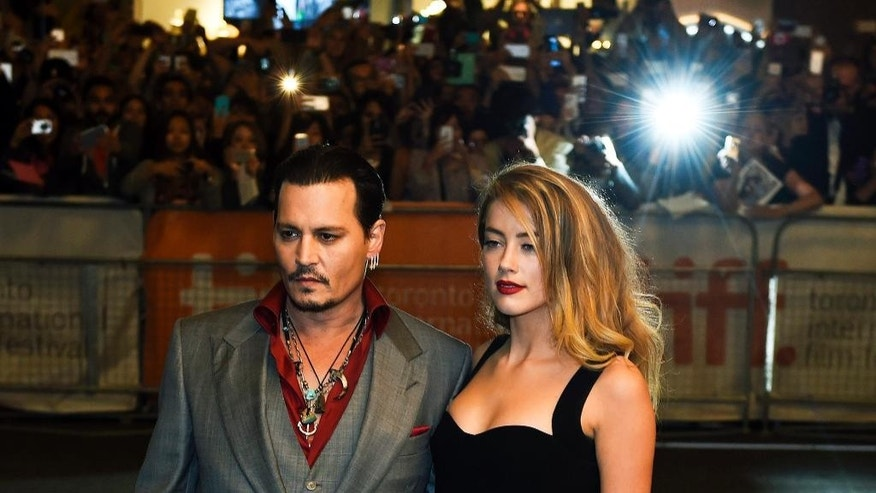 Actor Johnny Depp and wife Amber Heard pose for photographs on the red carpet for the new movie 'Black Mass' during the 2015 Toronto International Film Festival on Monday, Sept. 14, 2015.  (Nathan Denette/The Canadian Press via AP)