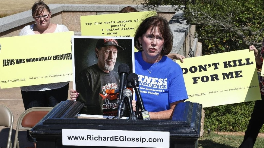 Nancy Vollertsen holds a photo of her brother, Greg Wilhoit, who spent five years on Oklahoma's death row before being exonerated, during a rally to stop the execution of Richard Glossip in Oklahoma City, Tuesday, Sept. 15, 2015. Glossip is scheduled to be executed Wednesday, Sept. 16, 2015. (AP Photo/Sue Ogrocki