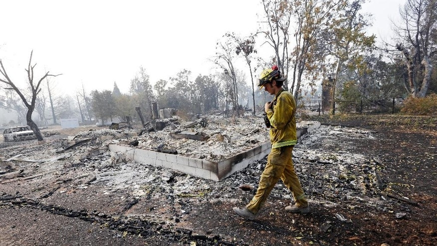 Firefighter Thomas Fitzpatrick walks past the remains of a house destroyed in a wildfire several days earlier, Tuesday, Sept. 15, 2015, in Middletown, Calif. The fire that sped through Middletown and other parts of rural Lake County, less than 100 miles north of San Francisco, has continued to burn since Saturday despite a massive firefighting effort. (AP Photo/Elaine Thompson)
