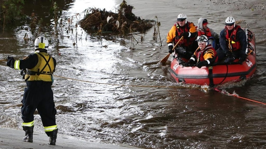 A swift-water rescue crew helps a man after he was stranded in a tree in the Los Angeles River near downtown Los Angeles on Tuesday, Sept. 15, 2015. Rescuers were looking for more victims possibly stuck in thick vegetation along the riverbank just north of downtown, in an area known for homeless encampments. A record-breaking storm slammed parched Southern California on Tuesday, sending rainfall gushing down roadways and turning the morning commute treacherous. (AP Photo/Richard Vogel)