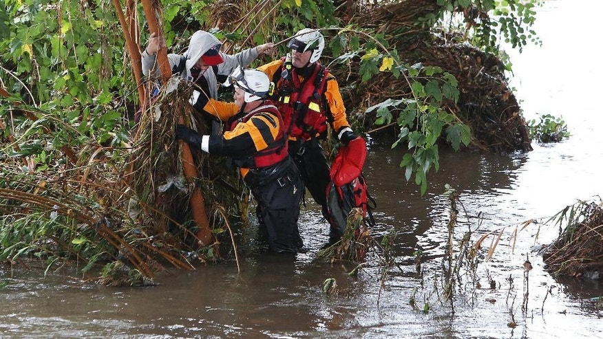 A swift-water rescue team helps a stranded man from a tree along the Los Angeles River near downtown Los Angeles, Tuesday, Sept. 15, 2015. Rescuers were looking for more victims possibly stuck in thick vegetation along the riverbank just north of downtown, in an area known for homeless encampments. A record-breaking storm slammed parched Southern California on Tuesday, sending rainfall gushing down roadways and turning the morning commute treacherous. (AP Photo/Richard Vogel)