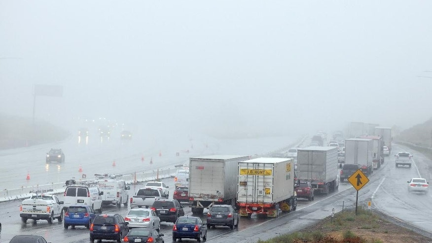 Traffic is slowed from the rain at the Cajon Pass and the Interstate 15 near Hesperia Calif.  on Tuesday Sept.  15, 2015. A record-breaking storm slammed parched Southern California on Tuesday, sending rainfall gushing down roadways and turning the morning commute treacherous.  (James Quigg/The Victor Valley Daily Press via AP) MANDATORY CREDIT