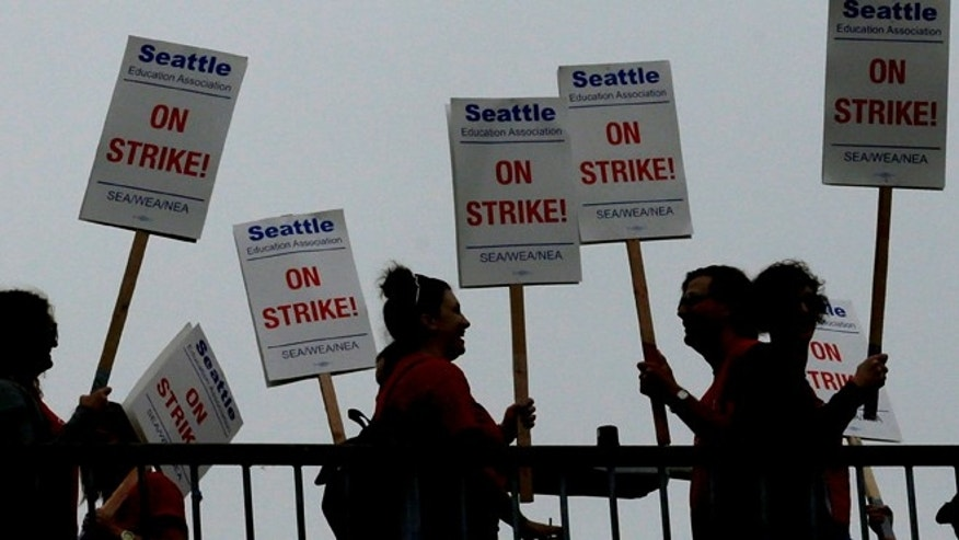Sept 10: Striking Seattle School District teachers and other educators walk a picket line on a pedestrian overpass.
