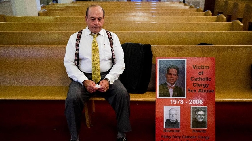 Arthur Baselice, the father of Arthur Baselice III, pictured in poster at right, sits on a pew after a news conference in Philadelphia on Wednesday, Sept. 16, 2015. Baselice said his son was abused by a priest and a religious brother, became addicted to drugs and killed himself. Baselice said the Vatican needed to find ways to hold church leaders accountable for sheltering predators. (AP Photo/Matt Rourke)