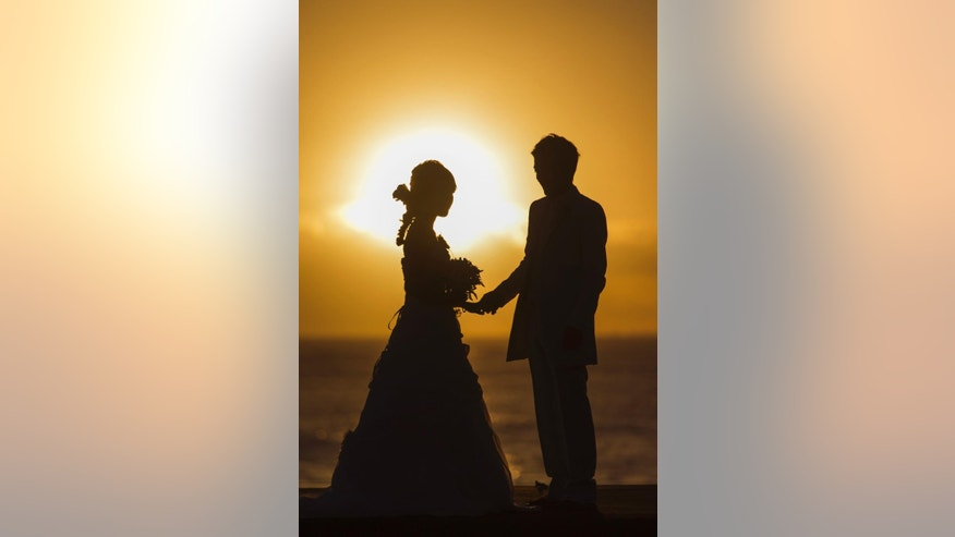 As the sun sets, a wedding couple is seen near the ocean, Wed. Sept. 16, 2015 in Honolulu.  A powerful magnitude-8.3 earthquake hit off Chile's northern coast Wednesday night putting Hawaii under a tsunami advisory.  (AP Photo/Marco Garcia)